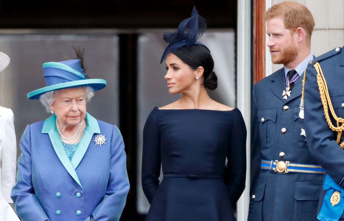 Queen Elizabeth II, Meghan, Duchess of Sussex and Prince Harry, Duke of Sussex watch a flypast to mark the centenary of the Royal Air Force from the balcony of Buckingham Palace on July 10, 2018 in London, England.