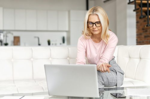 Brooding middle-aged woman using a laptop for remote work at home, studying online, a serious female mature teacher checking tasks on the computer