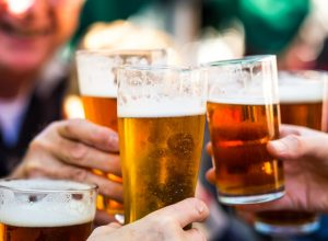 Close up color image depicting a group of people celebrating with a toast. The people cheers their glasses of beer (pints of beer) together in a gesture of celebration, togetherness and happiness. The people are defocused in the background, while focus is on the glasses of beer in the foreground. Room for copy space.