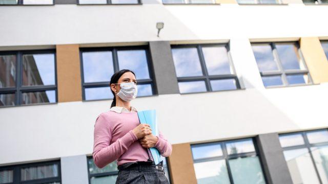 Teacher outside of a school wearing a mask