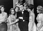 sean connery in black suit surrounded by women in james bond movie thunderball in a black and white still