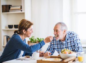 A senior couple eating breakfast