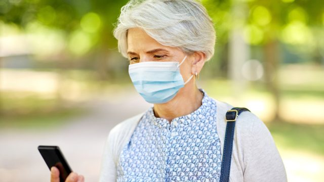 senior woman wearing medical mask for protection from virus with smartphone at park