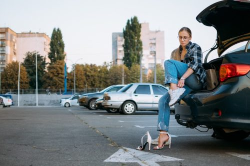 Woman changes shoes after driving a car