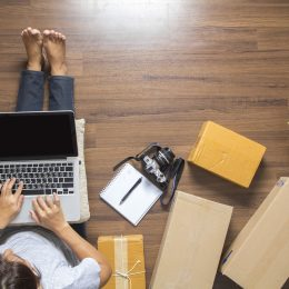 Person on computer surrounded by deliver boxes