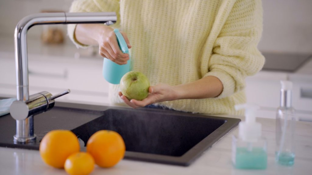 person spraying cleaning solution on fruit at sink