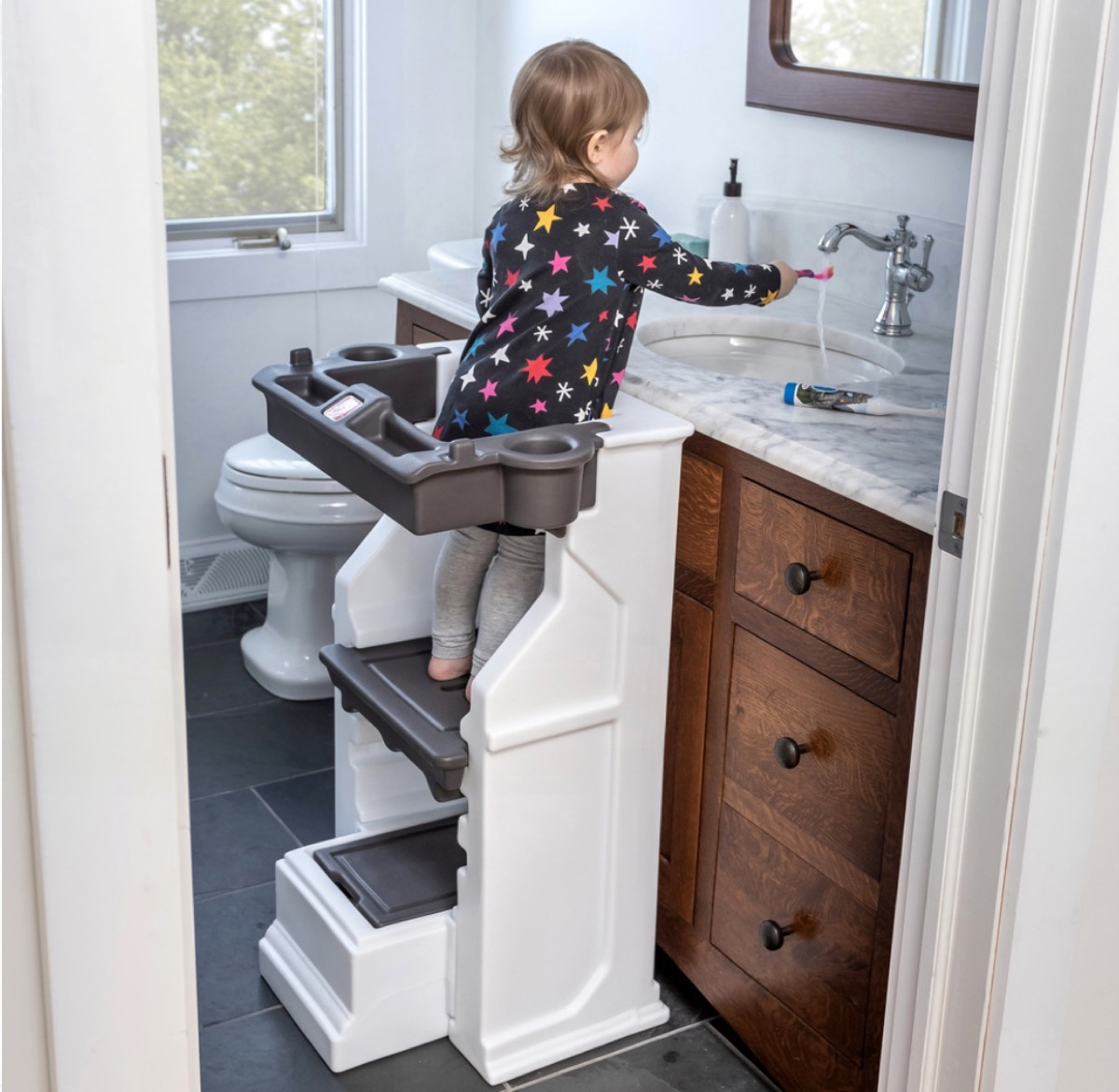 child standing on white and gray learning tower at bathroom sink