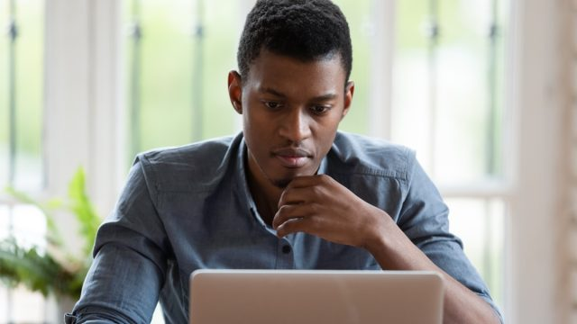 millennial male employee look at laptop screen working