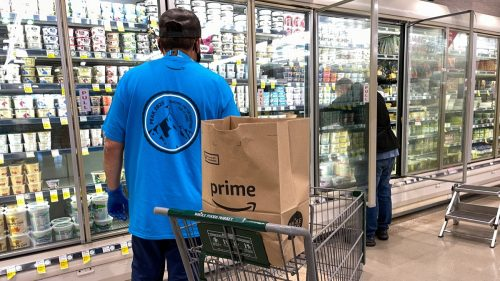 Orlando, FL USA - January 24, 2021: Amazon Prime Fresh employees shopping at a Whole Foods grocery store selecting food for for people to have delivered to their homes.