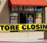 The front of a store going out of business with closing and liquidation signs