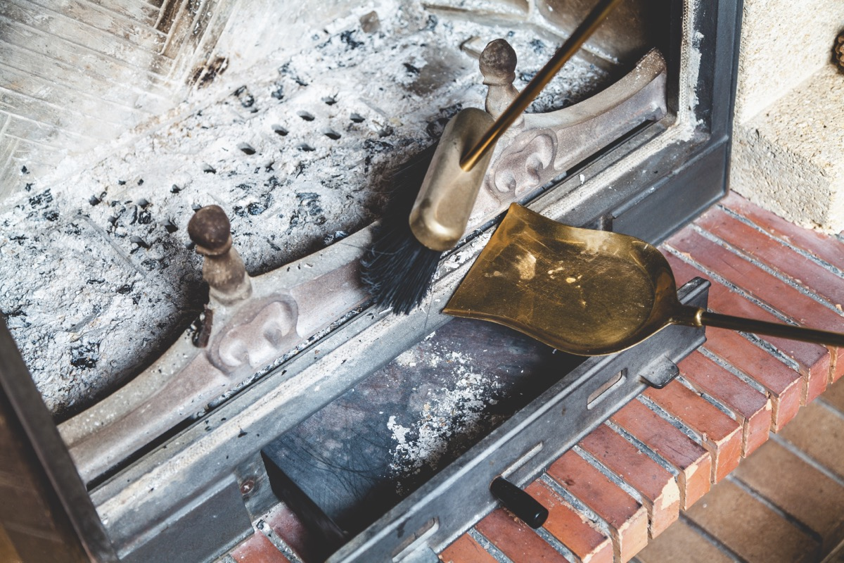 person sweeping fireplace ash into bronze pan