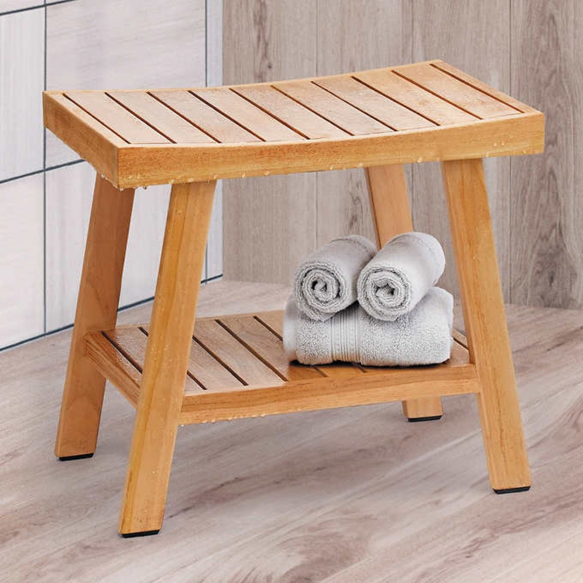 teak shower bench with white towels on its lower shelf