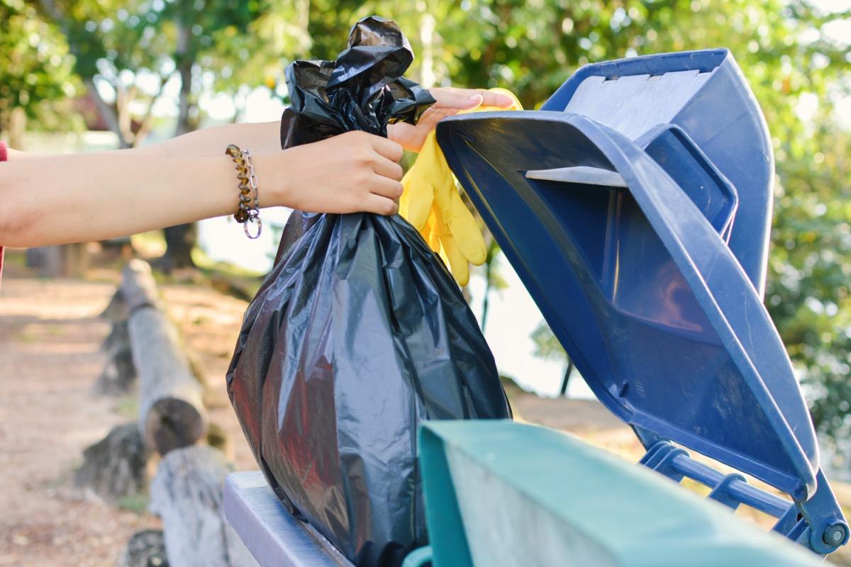 person throwing away black bag of trash