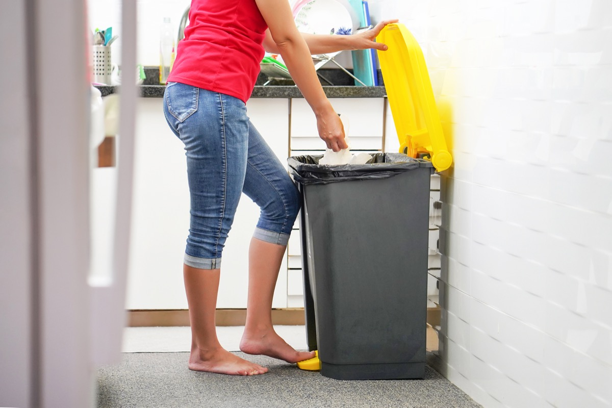 person throwing away trash in kitchen trash can