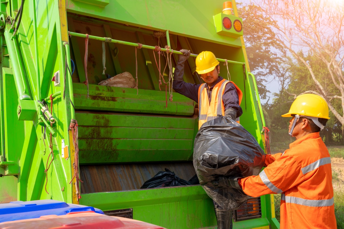 two garbage collectors loading black garbage bags into truck