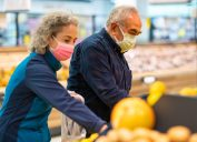The senior couple that goes shopping with protective face masks selects fruit and vegetables and fills them into shopping bags