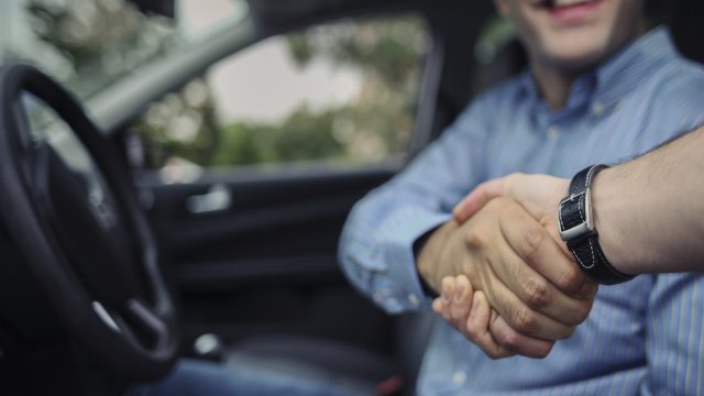 Driver shaking hands with seller after buying a used car