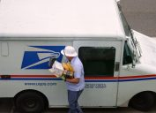 A mail carrier bringing boxes and envelopes from inside a mail truck