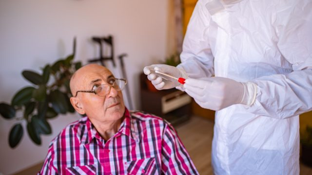 After the doctor in PPE finished with PCR testing, in the nursing home, he talks with a senior patient in the wheelchair explaining to him how to stay safe during the COVID-19 pandemic