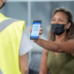 A person holds an iPhone in her hands and displays it to a guard. There is a green check mark and a bar code on her screen.