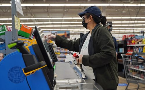Cromwell, CT / USA - April 20, 2020: Masked and gloved woman uses the self checkout