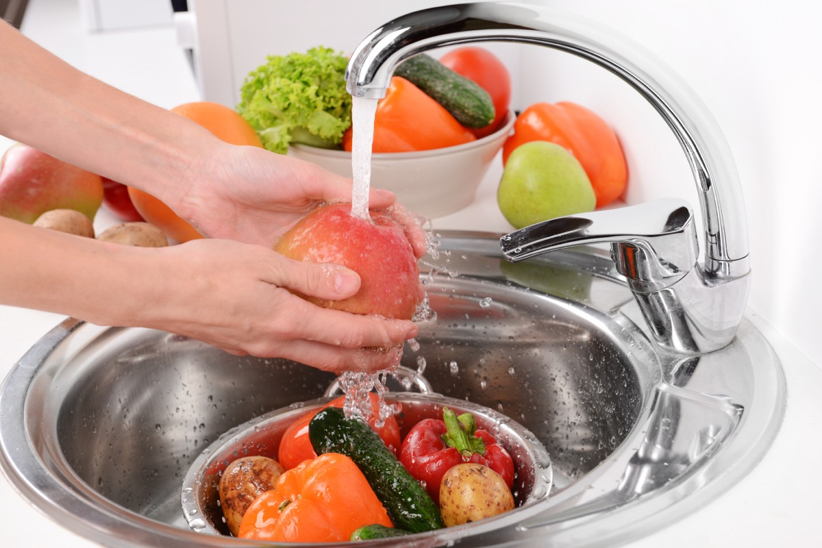 person washing fruits and vegetables in a metal kitchen sink