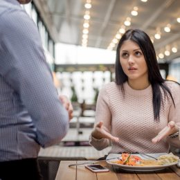 Women look at waiter and pointing at her food