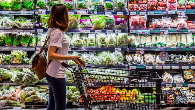 A woman is looking for organic vegetable in the shelf at supermarket.