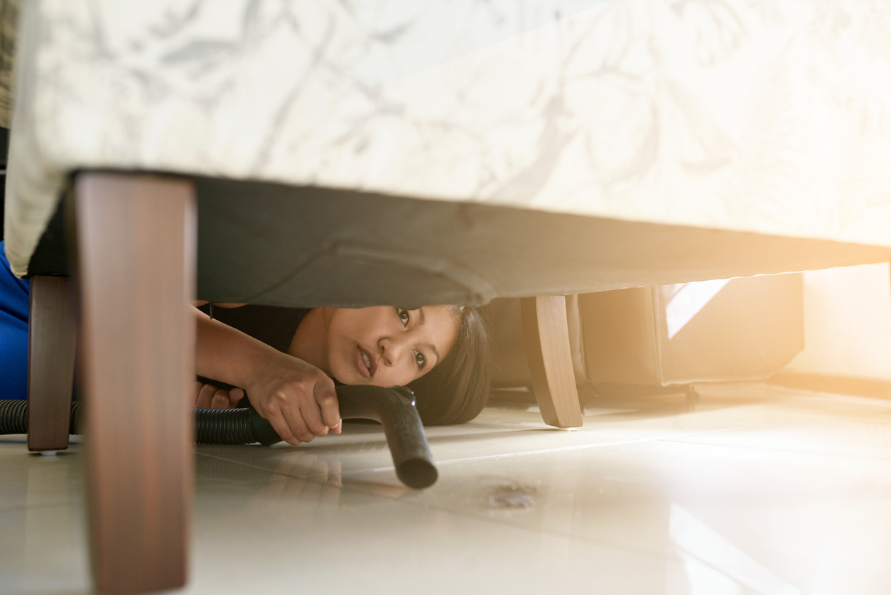 A woman lying down on the ground to clean under a chair with a vacuum