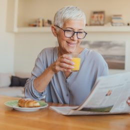 A senior woman drinking juice at breakfast while reading the paper