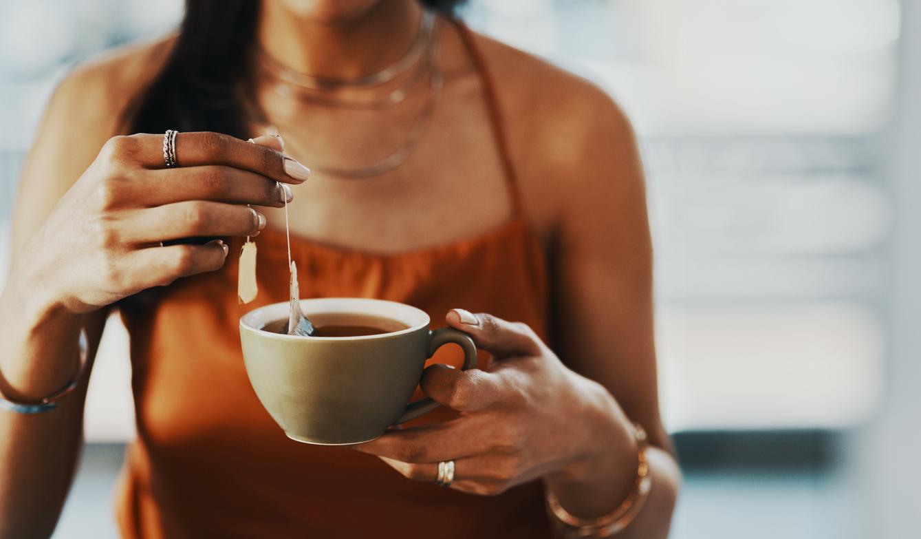 A close up of a woman brewing a tea bag into a tea cup