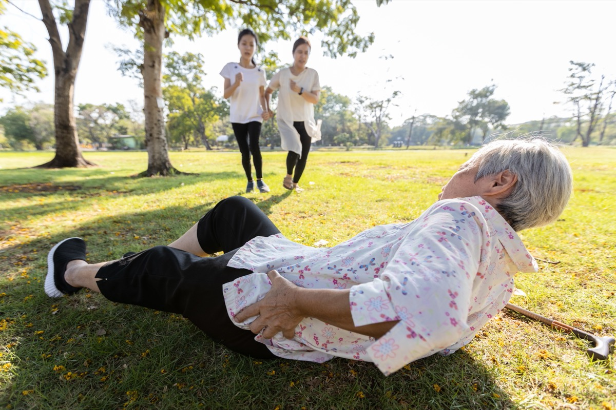 older woman hurts hip and falls in the grass as two younger women run toward her