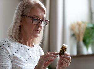 A senior woman holding a pill bottle while reading the label