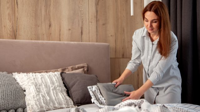 young woman making bed with multiple color sheets on it