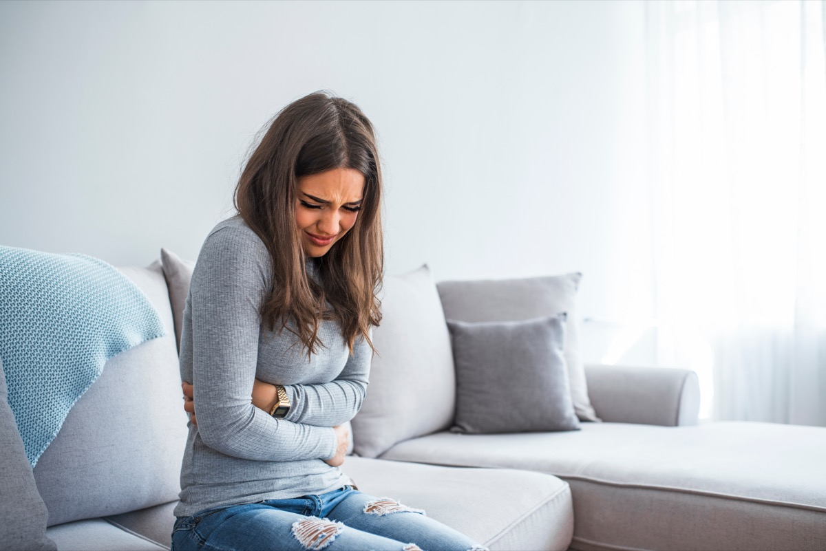 young woman in gray shirt and jeans with stomach pain on couch
