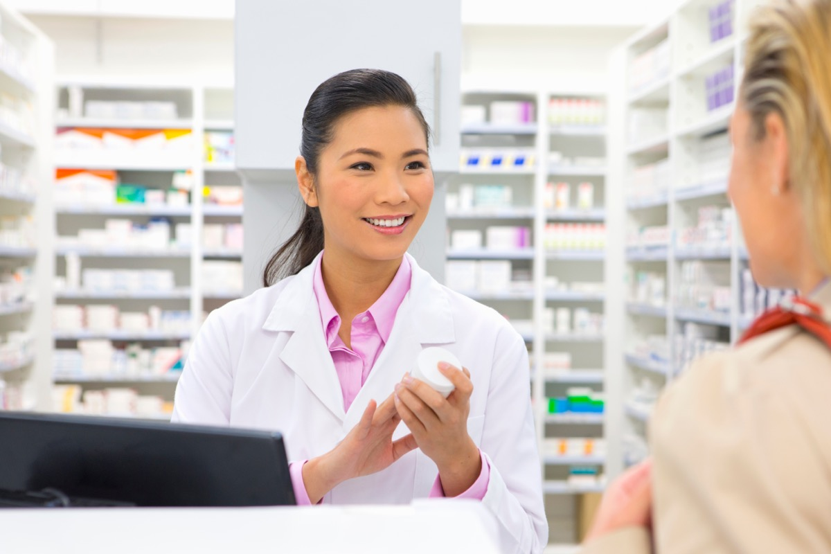 woman talking to pharmacist who is holding white prescription bottle