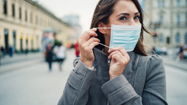 A young woman putting on a face mask while walking down the street