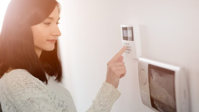 A woman using a keypad for a home security system