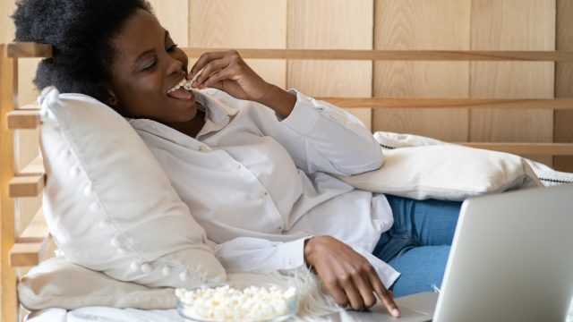 A young woman sitting in bed while watching a streaming service on her laptop and eating popcorn
