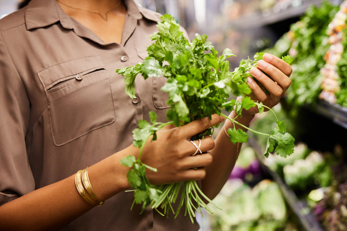 Close-up of a woman examining a bunch of parsley in the fresh produce section in a supermarket