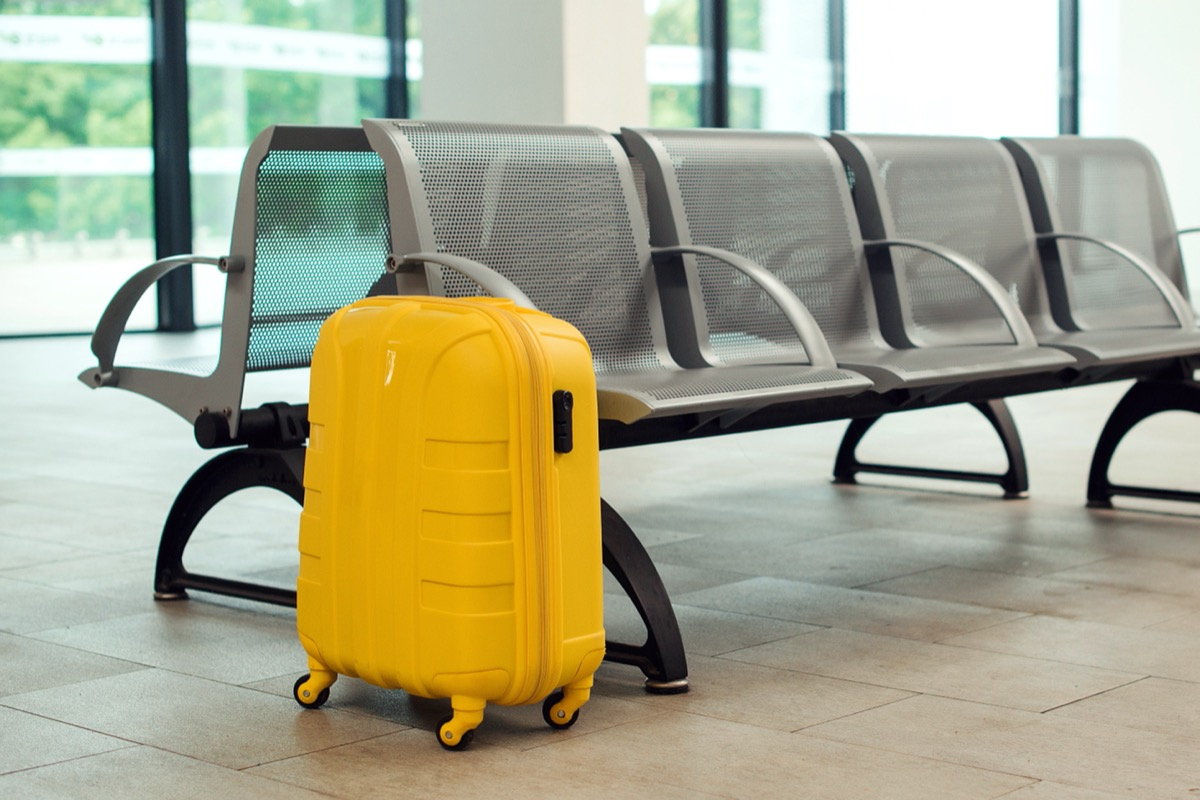 yellow hard-sided suitcase alone at airport