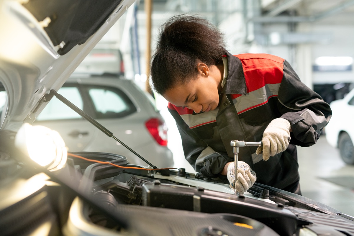 young female mechanic working on car