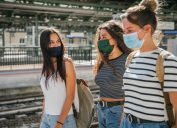 A group of young women walking through an outdoor train station while wearing masks