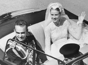 Prince Rainier and Grace Kelly waving to the crowd from an open car after their wedding in April 1956