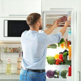 Man taking meat from fridge
