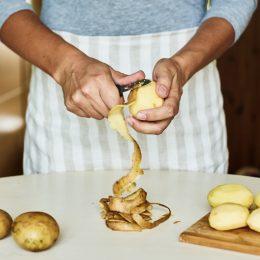 person in blue shirt peeling potatoes