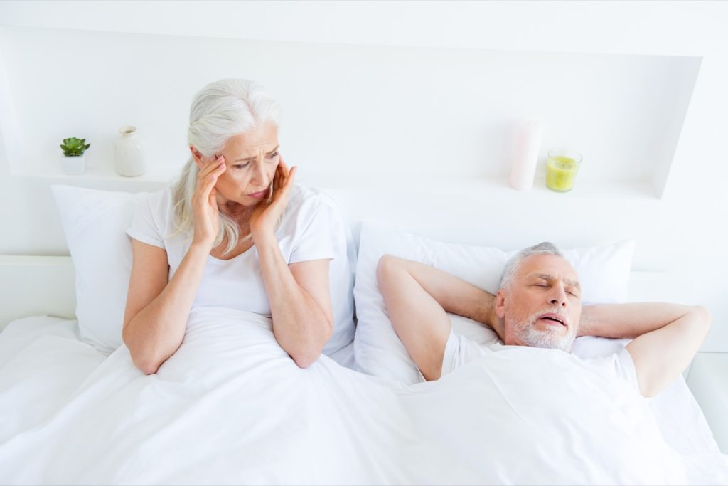 Older couple in bed, woman awake looking annoyed at man