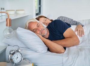 Older couple sleeping in bed