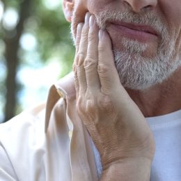 Close up of senior man holding jaw in discomfort or pain