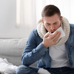 Young man coughing into a napkin